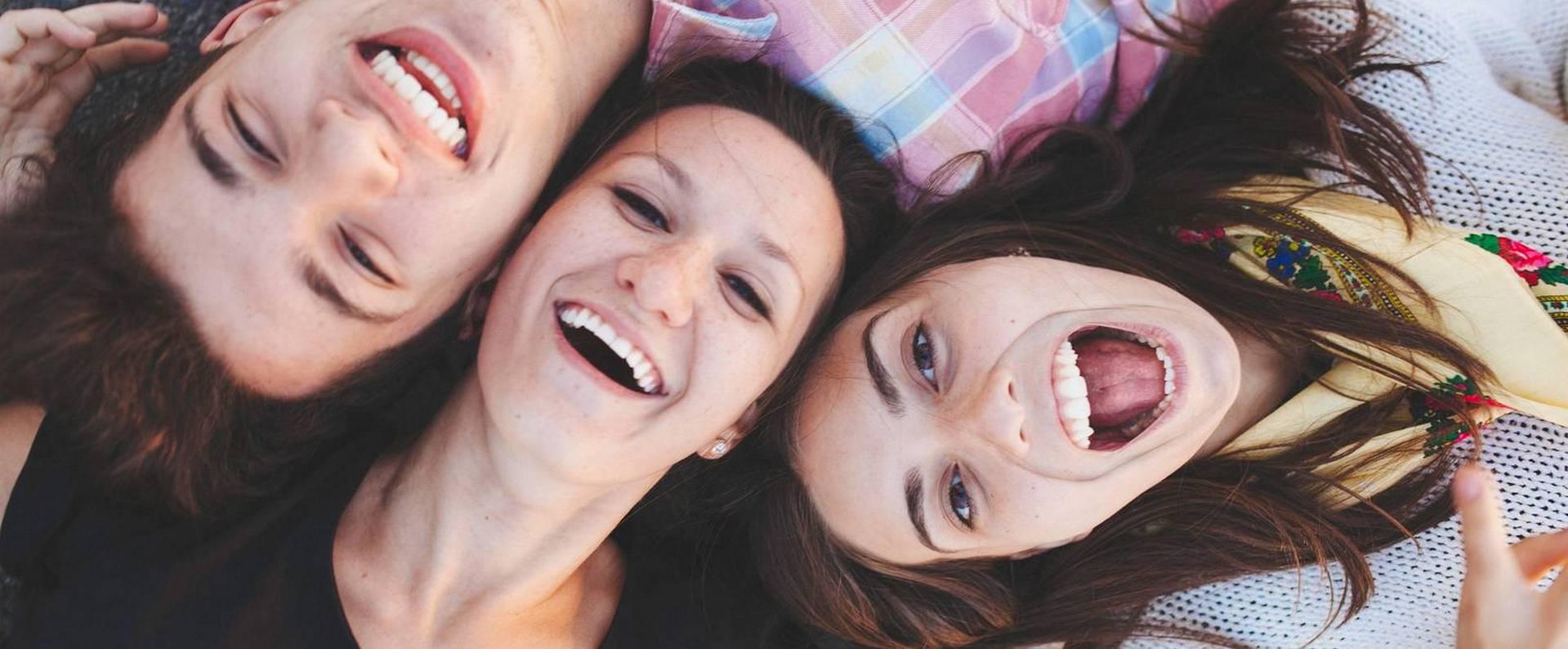 Nahaufnahme dreier bester Freunde, die auf dem Boden liegen und lachen. Jugendliche in Alltagskleidung lachen in die Kamera, von oben aufgenommen